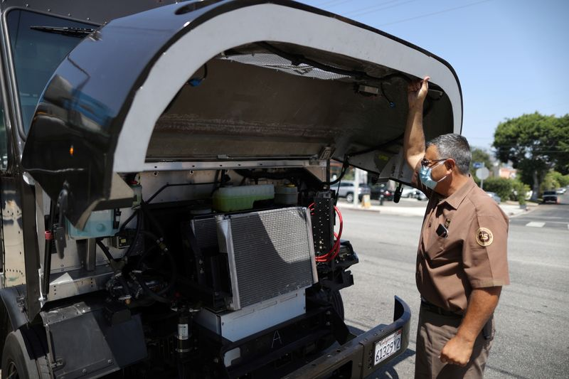 UPS Driver Gilbert Lopez opens the hood of an electric UPS truck, amid the global outbreak of