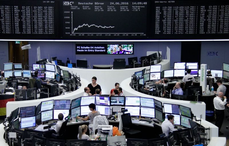 Traders work at their desks in front of the German share price index, DAX board, at the stock