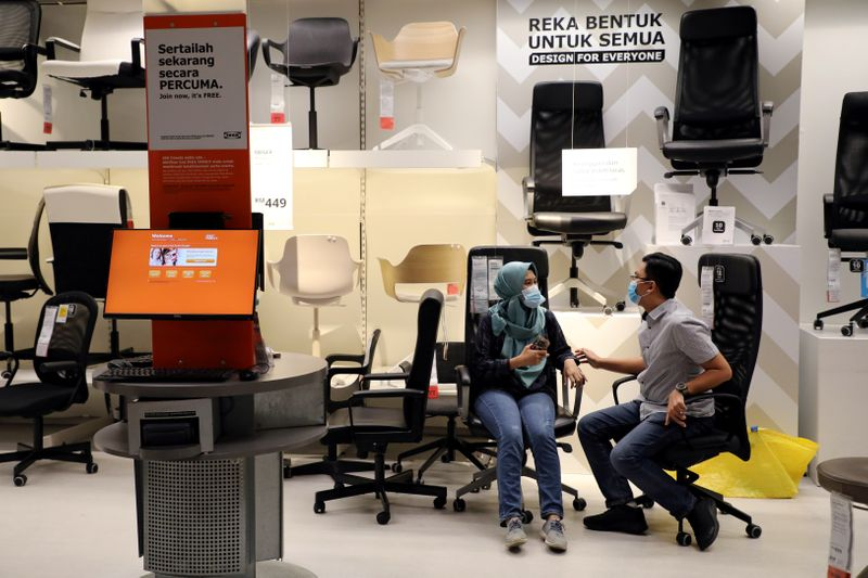 FILE PHOTO: Customers wearing protective masks shop for office furniture at IKEA, amid the