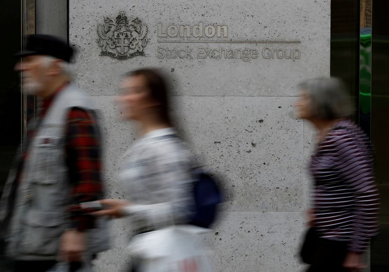 FILE PHOTO: People walk past the entrance of the London Stock Exchange