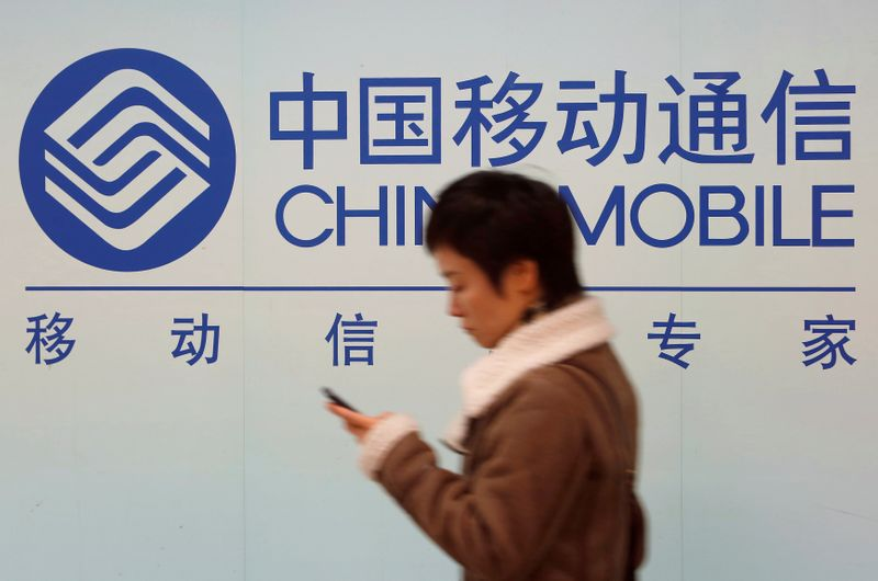 FILE PHOTO: A woman looks at the screen of her mobile phone while walking past a China Mobile