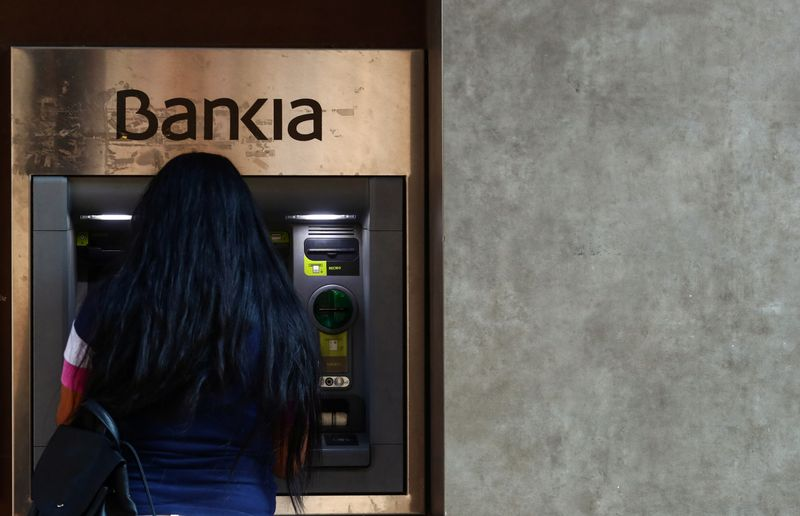A woman uses an ATM machine at the branch of Bankia in Madrid