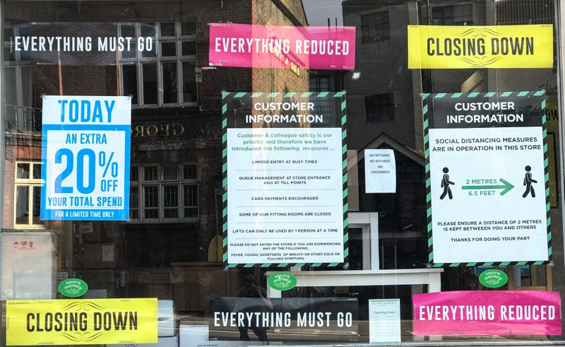 Closing down, reductions and social distancing posters are seen in a closed retail shop window