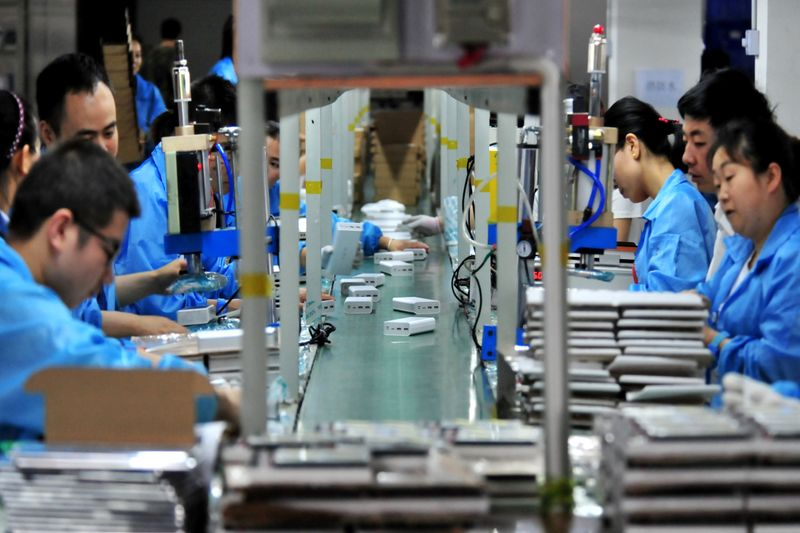 FILE PHOTO: Employees work on a production line manufacturing lithium battery products at a