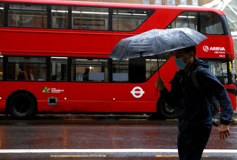 FILE PHOTO: A man with an umbrella walks past a bus in the City of London financial district