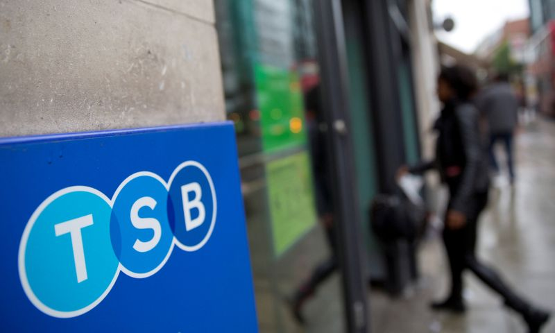 FILE PHOTO: A woman walks into a branch of TSB bank in London