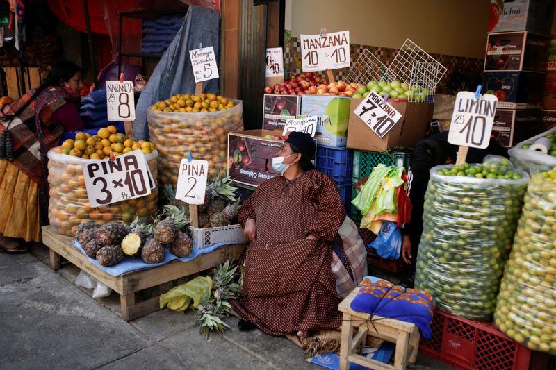 Fruit vendors chat at a street market in La Paz