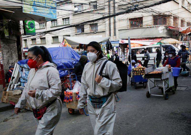 Women wear protective suits as they walk in a street in La Paz