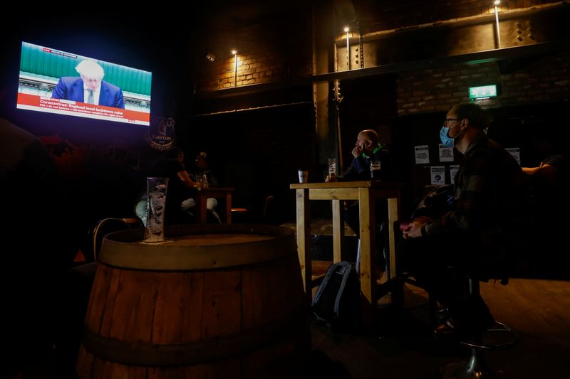 People watch Britain's Prime Minister Boris Johnson making a speech, at a pub, amid the