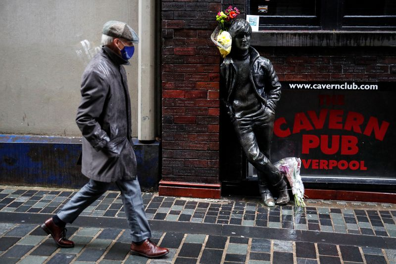 A man wearing a face mask walks past John Lennon statue in Liverpool
