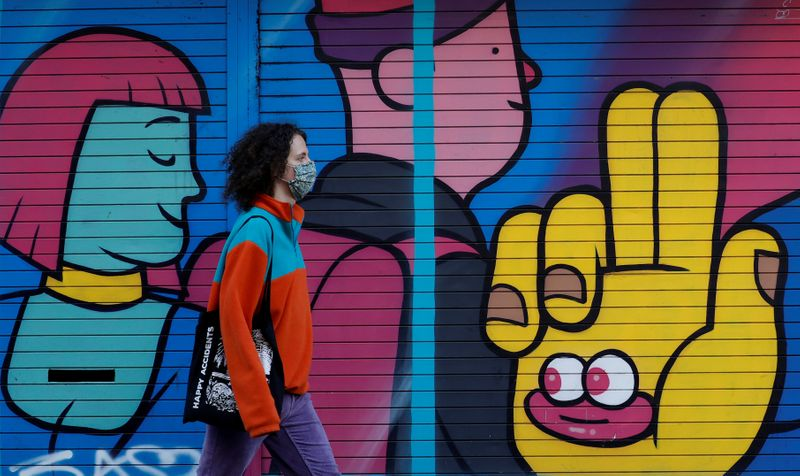 FILE PHOTO: A woman wears a face mask as she walks past a mural on a closed shop following the