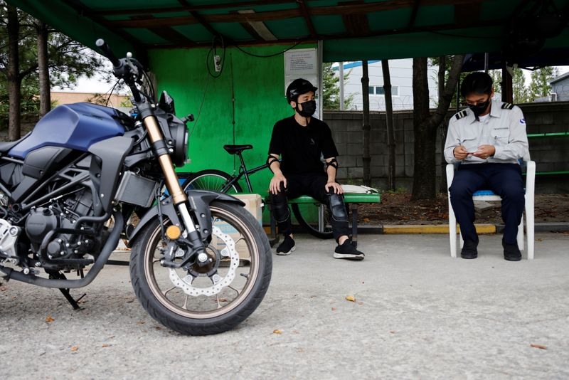 You Young-sik talks with a motorbike instructor during a training session amid the coronavirus