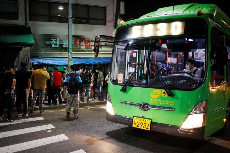 A bus driver looks on as day workers gather to seek for a job in Seoul