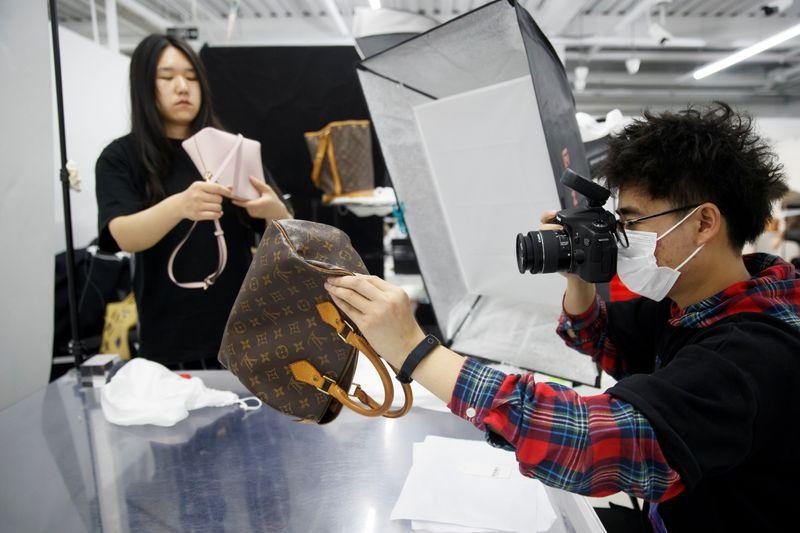 Staff member photographs handbags for the second-hand luxury goods retail platform Plum in