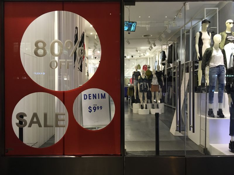 tAn H&M store has sale signs in the window in New York City