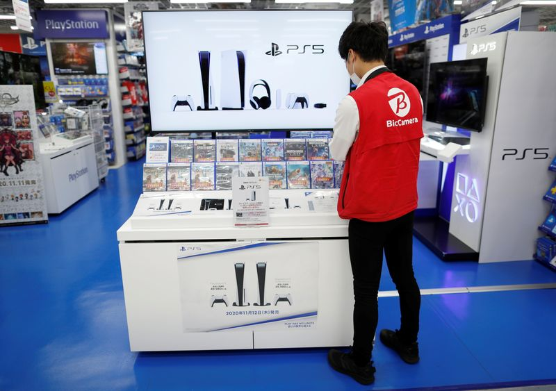 An employee works at the promotion display for the Sony PlayStation 5 game console and its