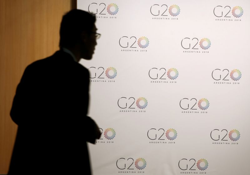 FILE PHOTO: A man stands next to a board with the G20 Meeting of Finance Ministers logo in