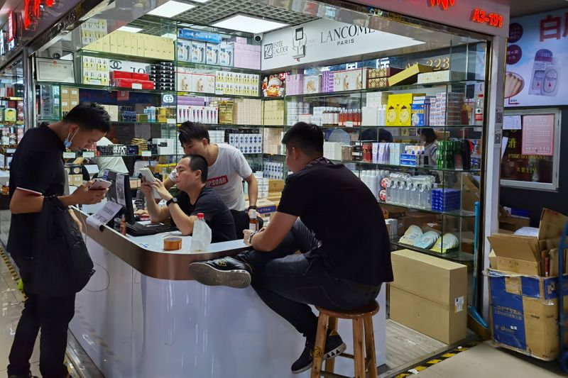 Cosmetics sellers check an order with a customer at the Mingtong Digital City market in