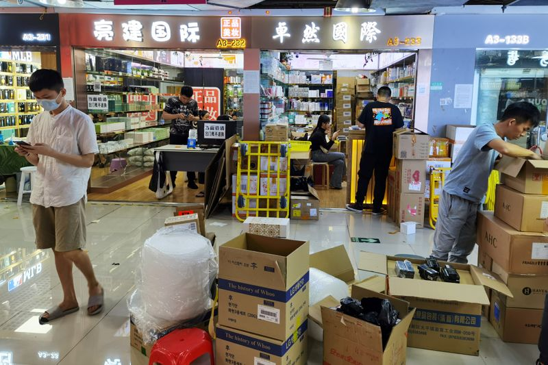 Boxes of cosmetics are unloaded at the Mingtong Digital City market in Shenzhen's Huaqiangbei