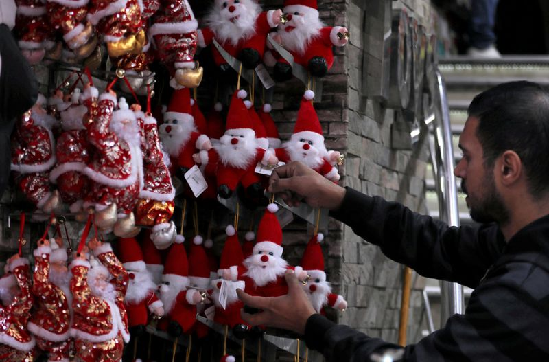 FILE PHOTO: Man looks at Santa Claus toys in a Christmas decorations shop in Cairo