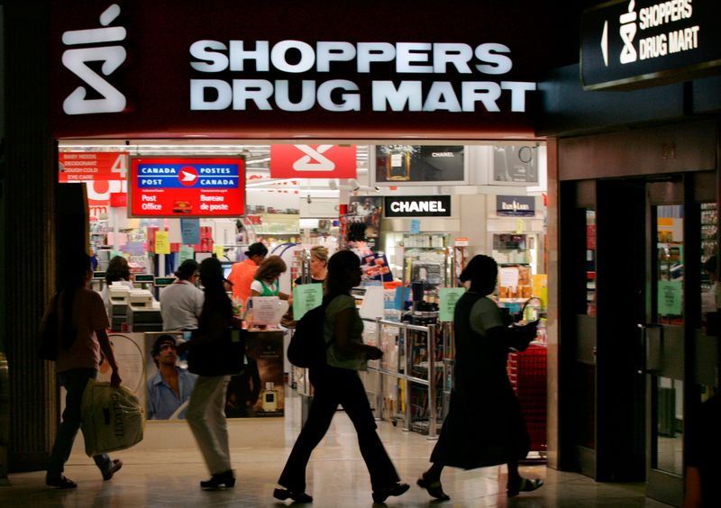 FILE PHOTO: People walk past a Shoppers Drug Mart store in Toronto