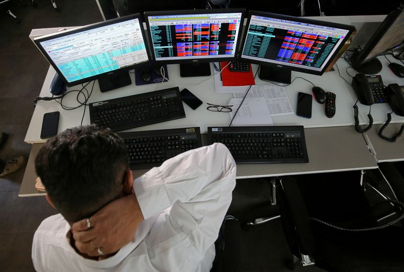 FILE PHOTO: A broker reacts while trading at his computer terminal at a stock brokerage firm in