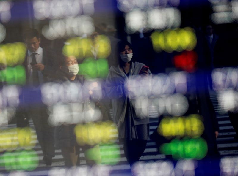 FILE PHOTO: Pedestrians wearing facial masks are reflected on an electric board showing stock
