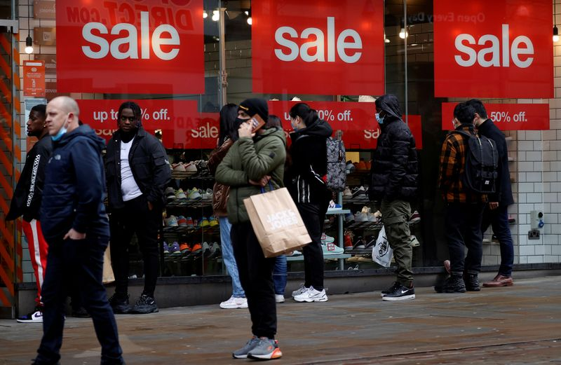 FILE PHOTO: Shoppers queue to enter a shoe shop at the start of the Boxing Day sales amid the