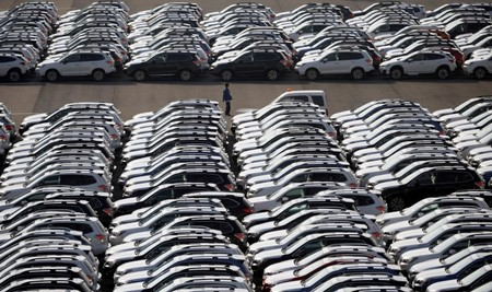FILE PHOTO A worker is seen among newly manufactured cars awaiting export at port in Yokohama