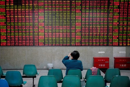 FILE PHOTO: An investor looks at an electronic board showing stock information at a brokerage