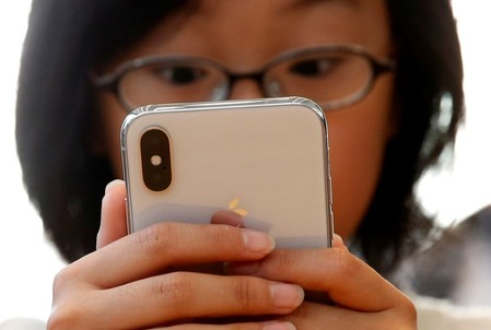 A customer looks at Apple's new iPhone X after it goes on sale at the Apple Store in Tokyo