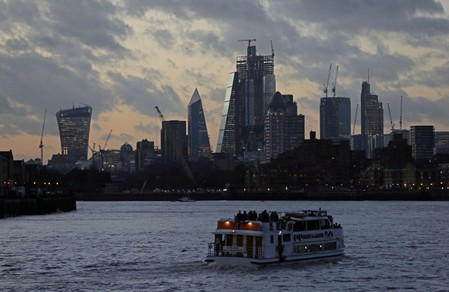 FILE PHOTO: A river boat cruises down the River Thames as the sun sets behind the Canary Wharf