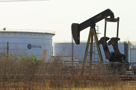 FILE PHOTO: An oil pumpjack and a tank with the corporate logo of state oil company PDVSA are